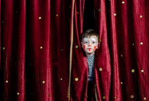 39419982 - young boy wearing clown make up peering out through opening in red stage curtains